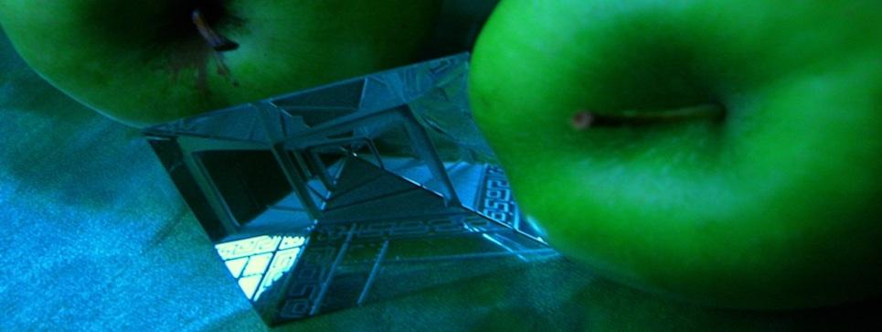 Drei grüne Avalon-Äpfel und ein Labyrint aus Glas als Symol für das Labyrint des Lebens